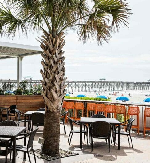 outdoor dining area in waterfront restaurant beside a long pier jutting out into the water