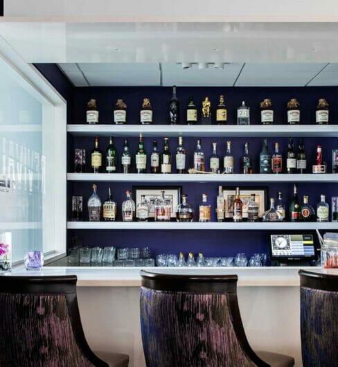 three bar chairs sitting in front of small corner bar
