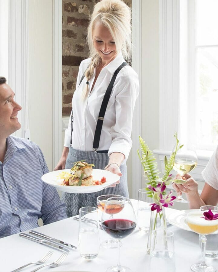 woman serving table of dining guests