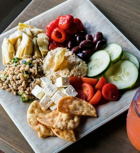 plate full of fresh veggies, cheese, grains, and dip appetizer next to orange cocktail