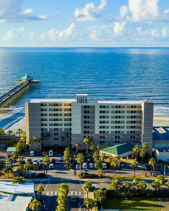 Tides Folly Beach Hotel Exterior of building directly on a beachfront beside a long pier reach out into the water