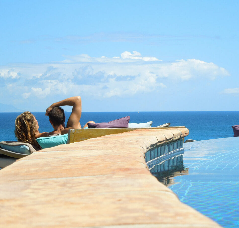 Couple rest in pool lounge chair on sunny, tropical day