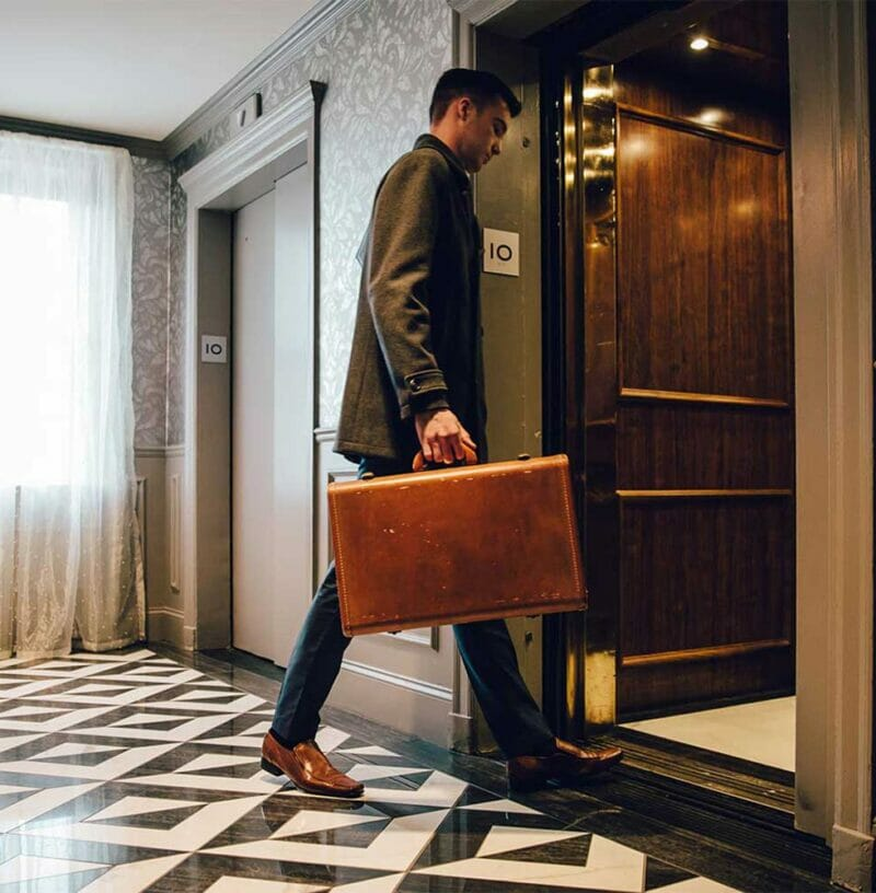 Male hotel guest enters elevator with leather briefcase