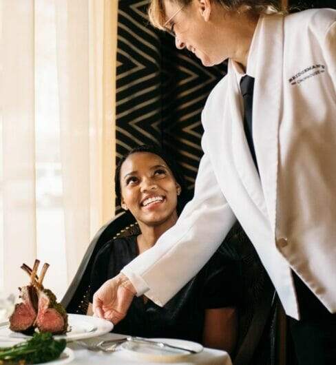 server delivering dish to seated dining guest