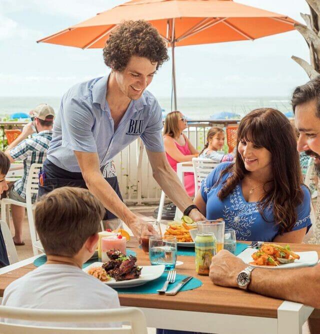 man serving dining family at outdoor restaurant