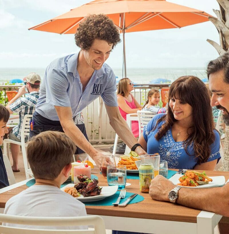man serving dining family at outdoor restaurant