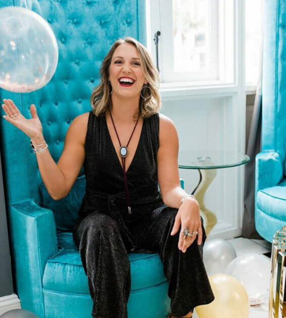 Woman sitting in tall velvet chair playing with clear balloon
