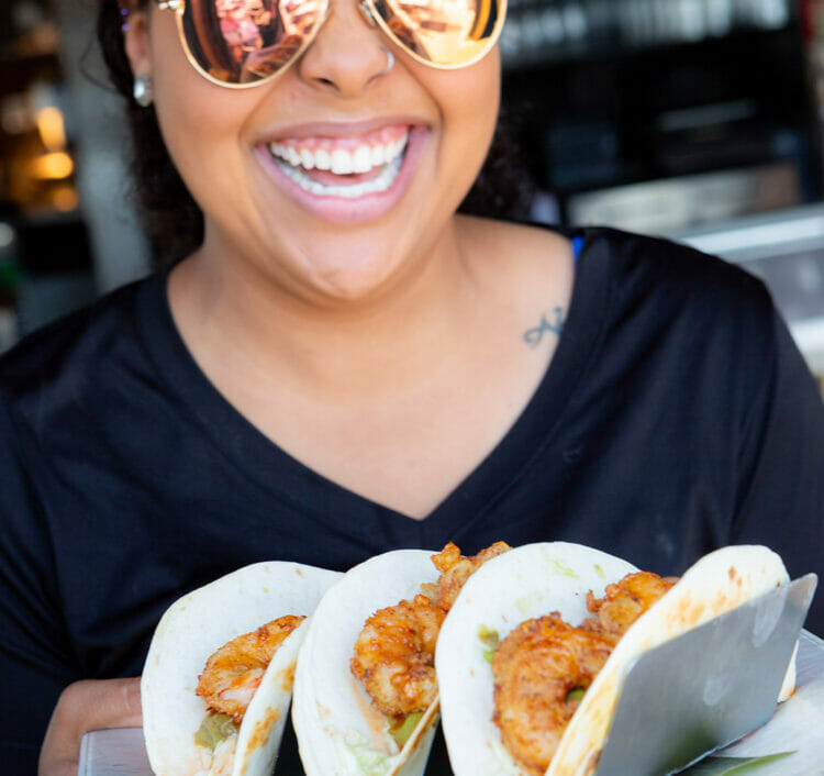 woman smiling holding three shrimp tacos