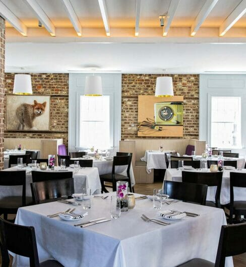 indoor dining room with brick walls and tables with white tablecloths