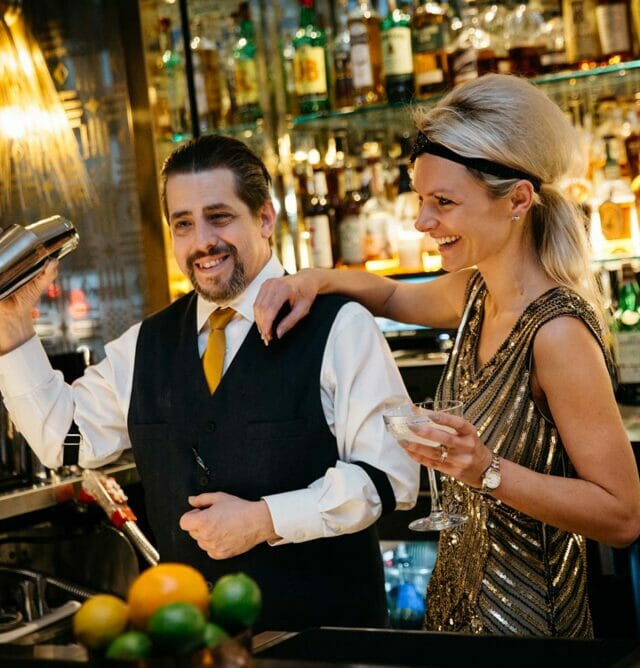 two bartenders mixing drinks while wearing old hollywood costumes