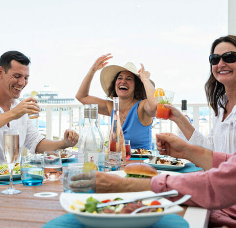 friends gathered around outdoor dining table next to waterfront