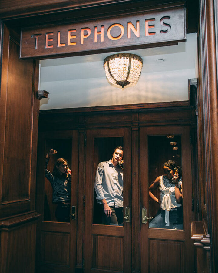 three friends standing in old telephone booth