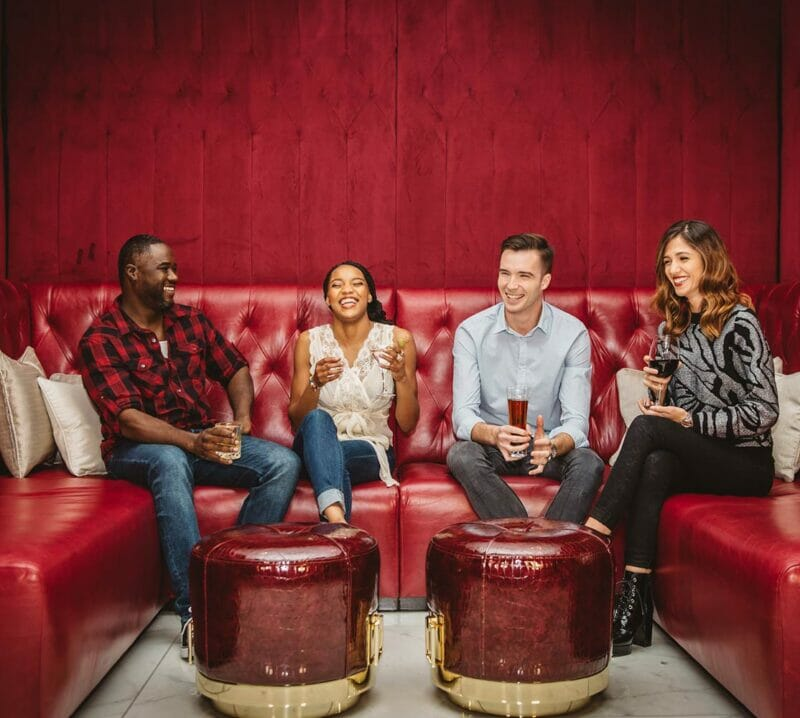 four friends sitting in bar lounge seating smiling
