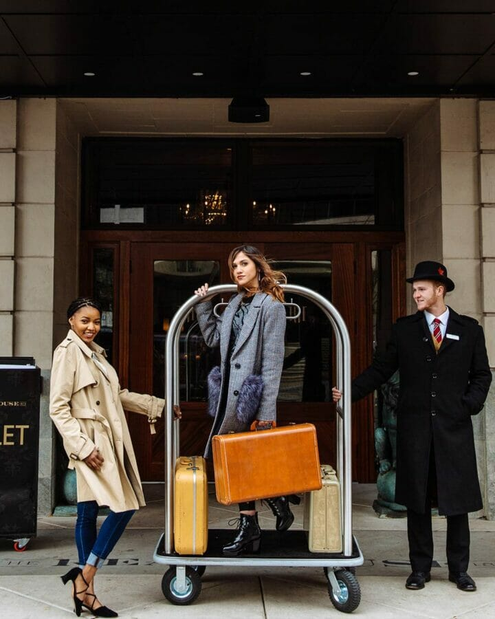 three people standing infront of hotel entrance with lobby luggage cart