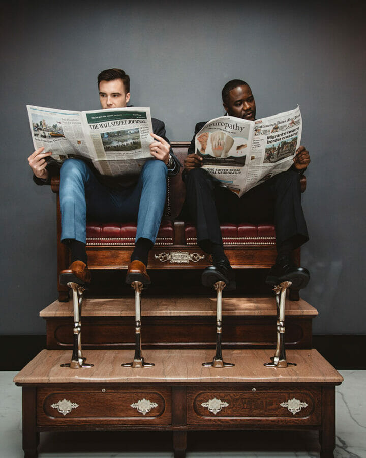 two men sitting in shoe shine seats while reading newspaper