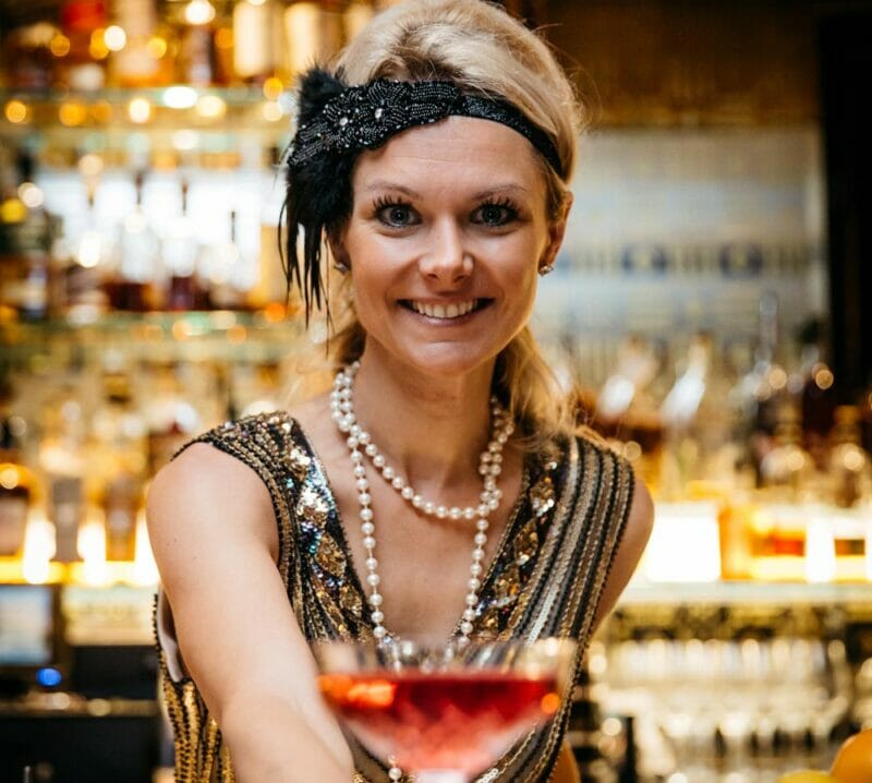 Flapper dressed bartender passes over tall cocktail